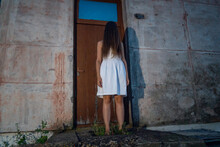 Girl In A White Dress With Long Dark Hair Thrown Over Her Face Stands On The Steps Of An Abandoned Building. Concept Of Horror, Mysticism