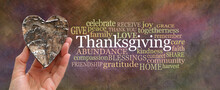 Put Some Love Into Thanksgiving Word Cloud Concept - Hand Holding A Rustic Brown Wooden Heart Beside A THANKSGIVING Word Cloud On Oil Painted Warm Coloured Background