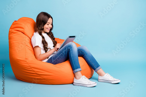 Obraz Portrait of nice attractive cheerful cheery focused wavy-haired girl sitting in chair using tablet ebook isolated on bright vivid shine vibrant blue teal turquoise color background - fototapety do salonu