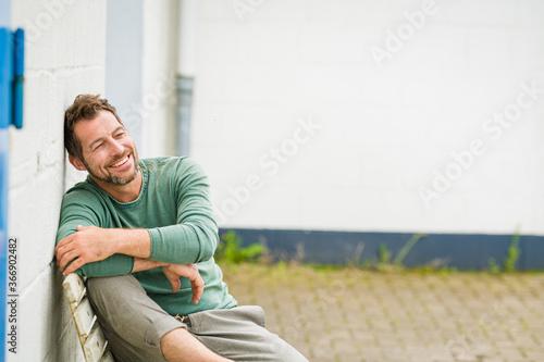 Foto Mann sitzt entspannt auf einer Bank, und sieht positiv nach vorne,im Hintergrund