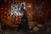 A Sorceress In A Black Dress In A Crown With A Veil Holds A Magic Ball In Her Hands. Pumpkins Are Licking On The Floor, An Old Witch's Book, And A Broomstick Stands Against The Wall. Fantasy