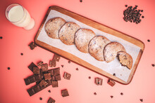 Freshly Made Chocolate Chip Cookies On A Wooden Serving Board. Cookies With A Glass Of Fresh Milk On The Side Along With Chocolate Chips And Pieces Of Chocolate Around On A Pink Background.Freshly Mad