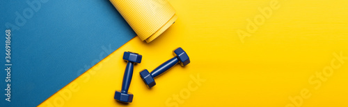 Fototapeta top view of blue fitness mat with dumbbells on yellow background, panoramic shot