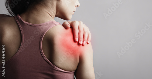 Obraz Young strong sporty woman suffering from pain in shoulder in sport wear. Touching the hand. Sports exercising injury. Closeup portrait with highlighted in red and empty space. Back view. The concept - fototapety do salonu