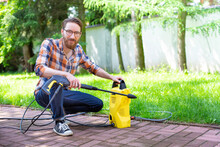 Man Using A High Pressure Washer In The Backyard, On A Sunny Day.