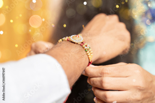 Платно Closeup of hands, sister tying rakhi, Raksha bandhan to brother's wrist during f