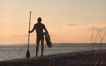 A Surfer With A Paddle Board Standing On The Shore. Back View. Bay In Background.