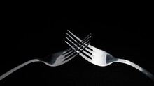 Two Forks Crossed On A Dark Ba...
