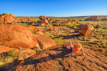 Outback, Northern Territory, Australia. Tourist Woman Rests After The Trek To The Top View Of Karlu Karlu Devils Marbles. Traveler Looking Panorama Over Granite Boulders At Sunset Light.