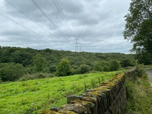 A Moss Covered Dry Stone Wall, Running Alongside A Country Lane, With A Large Field, And Forest Beyond In, Elland, UK