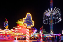 """Night Atmosphere With Spinning And Illuminating  Amusement Ride, """"Octopus Or Breakdance, And Chain Carousel, With Long Exposure At Rheinkirmes In Düsseldorf, Germany."""