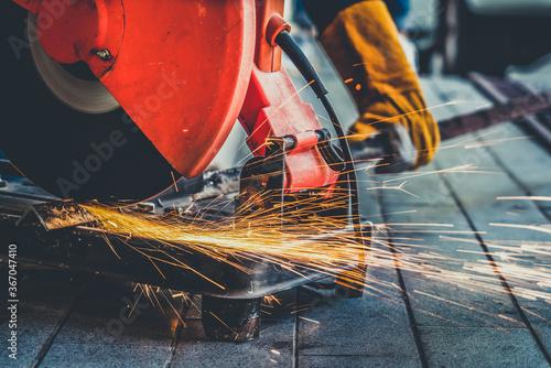 Fotografie, Obraz Professional mechanic is cutting steel metal with rotating diamond blade cutter