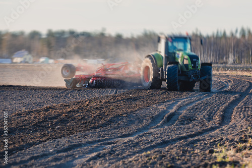Fotografia, Obraz Tractor with a disc harrow system harrows the cultivated farm field, process of