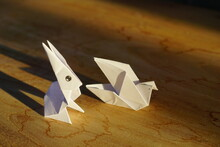 White Rabbit Origami On Wooden Background For Cover And Copy Space With Sunset Light Effect And Shadow