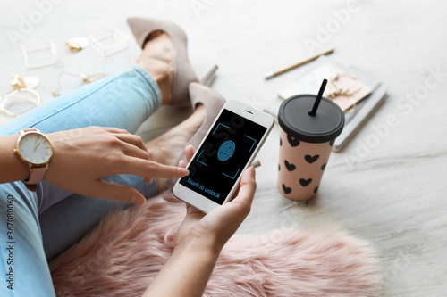 Obraz Woman holding smartphone with fingerprint sensor indoors, closeup. Digital identity - fototapety do salonu