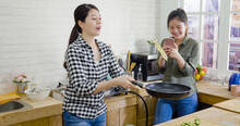 Two Female Friends Cooking And Taking Photo With Cellphone In Kitchen. Young Girl Flipping Pancake With Frying Pan While Roommate Using Mobile Phone Recording Video Of Making Process And Share Online