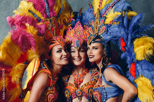 Fotografia, Obraz Three Women smiling portrait in brazilian samba carnival costume with colorful feathers plumage