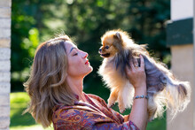 Medium Horizontal Back Lit Portrait Of Beautiful Young Woman Seen In Profile Holding Up Her Petite Orange Sable Pomeranian Dog In Exterior Garden Location During A Summer Late Afternoon