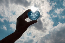 Hand Holding Up Blue Heart Against A Blue Sky With White Clouds.