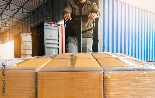 Fototapeta Worker unloading cargo shipment goods. package box, his using hand pallet jack load into a truck, Road freight transport, Warehouse industrial delivery shipment and logistics obraz