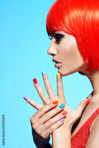 Profile portrait  of a fashion model with  red hairs and multicolor nails. - 367145068