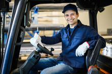 A Handsome Construction Worker Driving A Forklift In An Industrial Plant