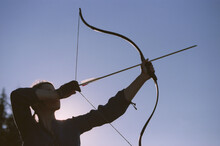 Woman Shooting With A Bow In The Mountains. Young Caucasian Female Archer Shooting With A Bow At Sunset. Scanned Film.