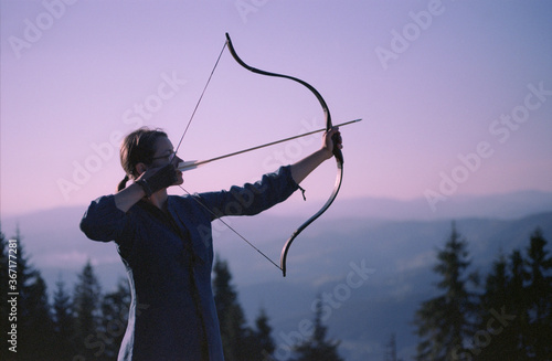 Fotografering Woman shooting with a bow in the mountains