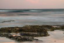 Long Exposure Shot. Surreal Blurred Sea Waves At Nightfall. The Shore, Ocean And Rocks With Enchanting Sunset Colors.