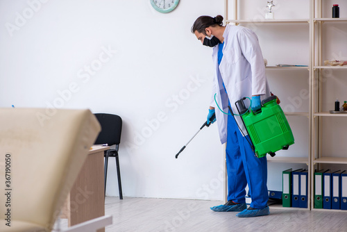 Cuadros en Lienzo Young male contractor disinfecting clinic in pandemic concept