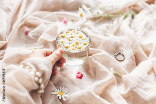 Fototapeta Hand with jewelry holding glass cup with daisy flowers in water on background of soft beige fabric with wildflowers