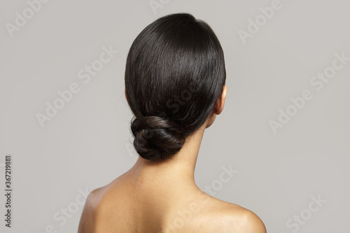 Fototapeta brunette with a smooth bun hairstyle from the back. on gray background obraz