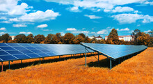 Solar Power Plant In Autumn. Solar Panels On Orange Grass Field Under Blue Sky With Clouds