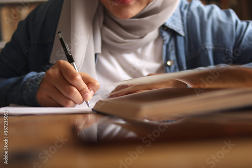 Asian muslim woman studying in library, exam preparation concept Fotobehang