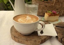 Latte Coffee On A Wooden Serving Tray With A Picnic Basket, Glass Of Water And Cheesecake In The Background