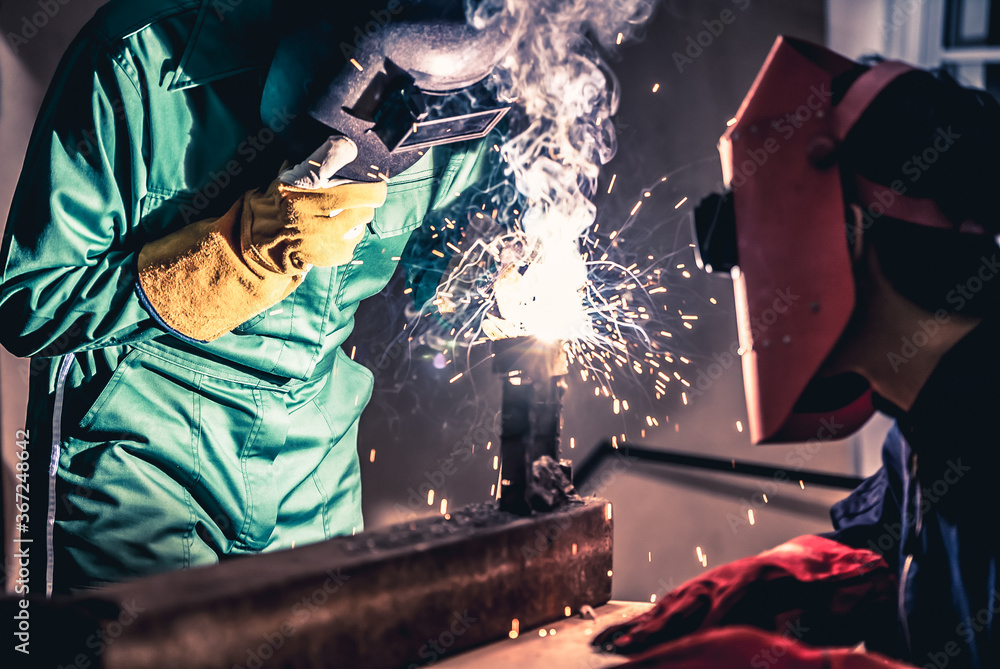 Fototapeta Metal welding steel works using electric arc welding machine to weld steel at factory. Metalwork manufacturing and construction maintenance service by manual skill labor concept.