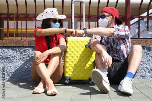 Obraz Handsome man and beautiful woman sit on pavement on platform of train station with yellow suitcase in protective mask fist to fist. T Couple wait for departure of train with luggage. - fototapety do salonu