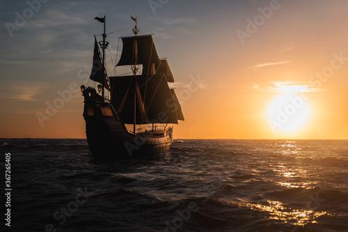 Foto ( 3D illustration, Rendering ) VIntage black pirate ship sailing towards the sunset