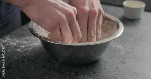 Fotografie, Obraz man mixing dough in steel bowl on concrete countertop