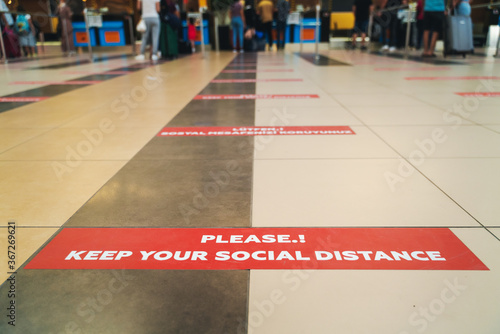 Obraz Sticker keep social distance on the floor in the airport check-in lobby, white letters on a red background travel in 2020 - fototapety do salonu