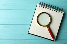 Top View Of Magnifier Glass And Empty Notebook On Light Blue Wooden Background, Space For Text. Find Keywords Concept