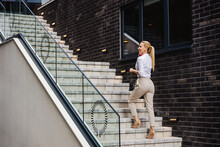Gorgeous Blond Smiling Fashionable Lady Ascending The Stairs And Talking On The Phone.