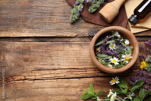 Flat lay composition with mortar and different healing  herbs on wooden table, space for text - 367271251