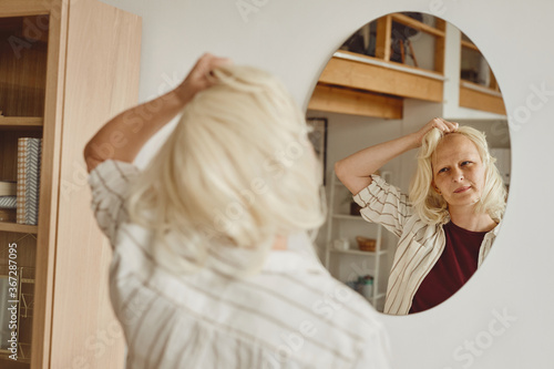 Warm-toned back view portrait of bald woman taking off wig while looking in mirr Fotobehang