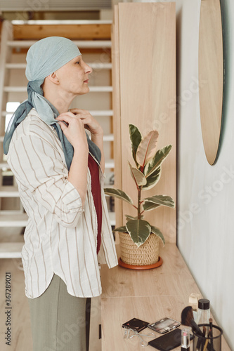 Vertical side view portrait of modern bald woman putting on head scarf while looking in mirror standing in home interior, alopecia and cancer awareness
