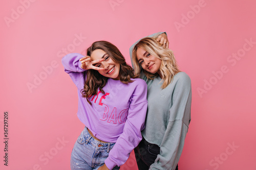 Fotografie, Obraz Pleasant curly young ladies posing on beautiful rosy background