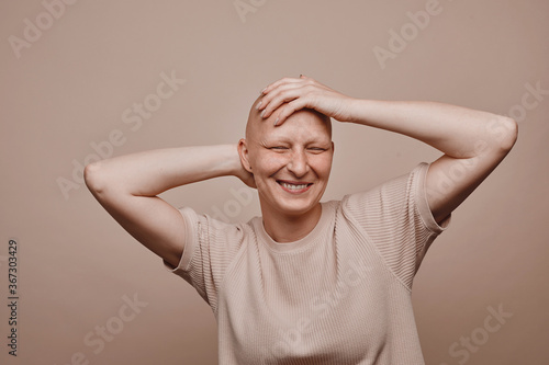Fotografie, Obraz Warm-toned waist up portrait of carefree bald woman touching shaved head and smi