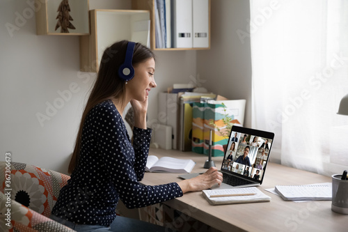 Smiling Caucasian female employee in headphones sit at desk at home talk on video call with colleagues, young woman have online webcam conversation virtual event with diverse multiethnic coworkers