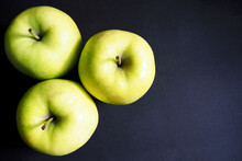 Three Large Green Gold Apples On A Black Background Top View . Organic Fruit