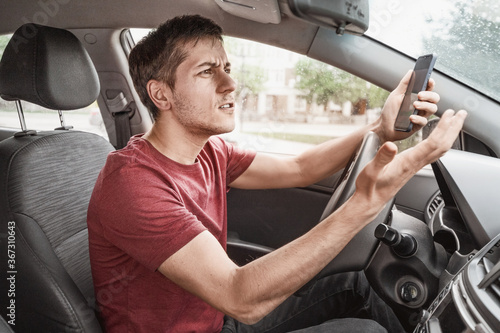 Fotografie, Obraz Man behind the wheel of his car loses concentration on the road situation and gets stuck in a smartphone typing SMS in a chat